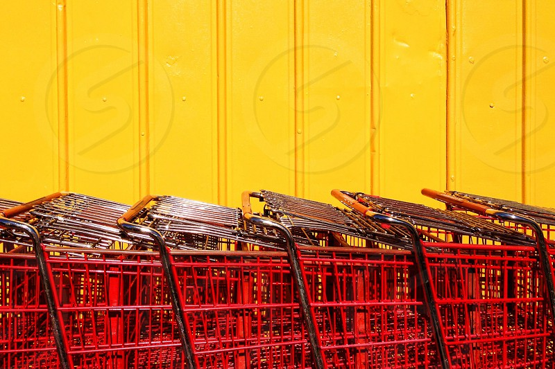 Red shopping carts are lined up against a yellow wall. photo