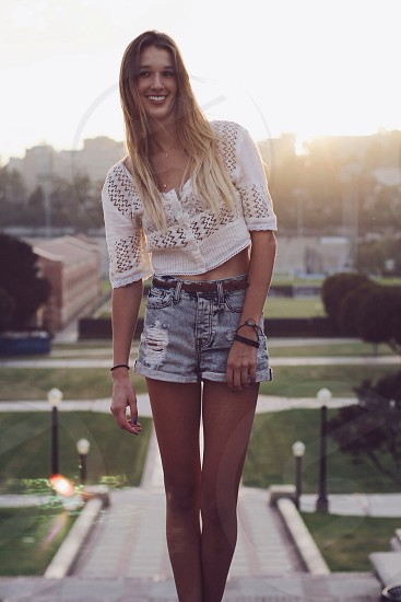 woman in white crop open weave sweater with distressed shorts photo