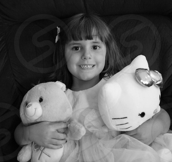 girl in white shirt lying and holding hello kitty lush and carebear plush photo