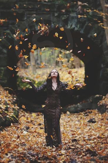 Girl under stone bridge throwing leaves photo
