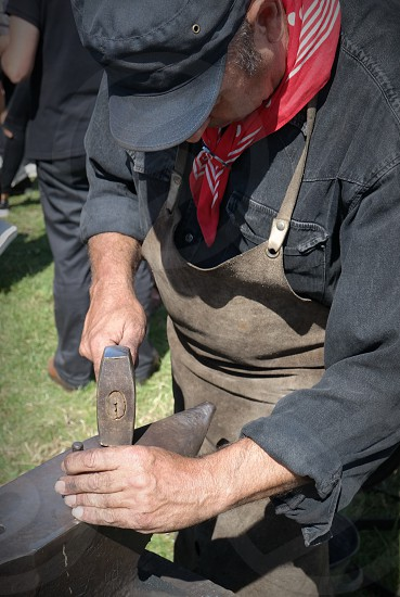 man wearing apron while holding hammer and working on anvil tool photo
