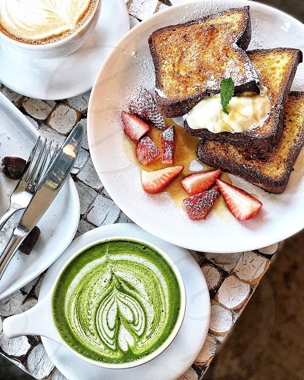 Matcha latte french toast with chopped strawberries and coffee at a cafe in NYC photo