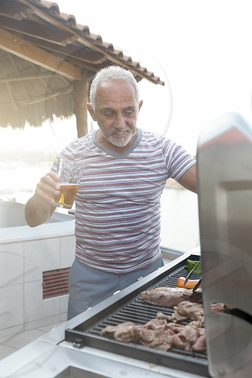 Caucasian man around 60 grilling meat and vegetables on a gas grill while enjoying a glass of beer photo