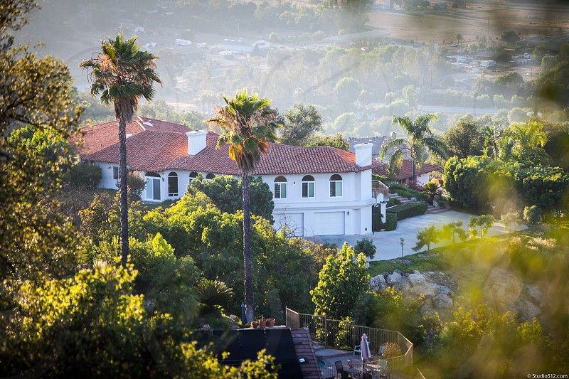 A luxury home in Southern California. Palm trees chimneys boulders driveway deck photo