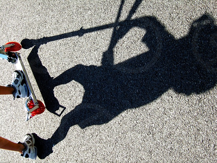 The feet and the shadow of a child riding a scooter with a handle ins seen at an angle on the sidewalk. photo