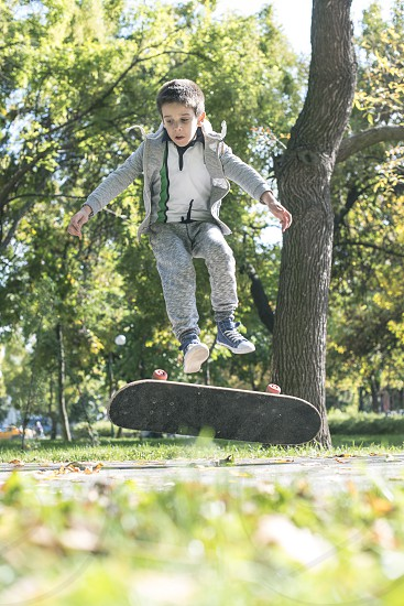 Boy with skateboard in the park. Autumn leaves photo