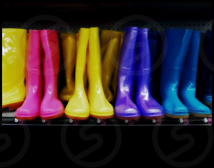 Boots for sale Bright neon pink and yellow and blue. Lined up on a shelf. photo