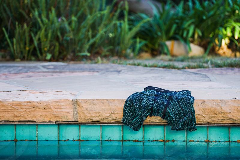 black shorts beside swimming pool beside green plants during daytime photo