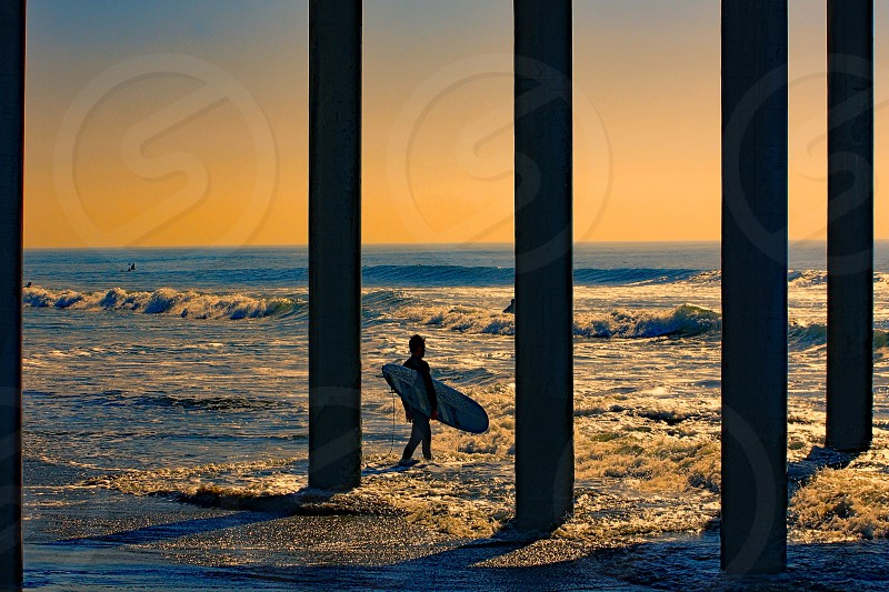 Silhouette of a surfer at sunset  walking under a pier into the ocean. photo