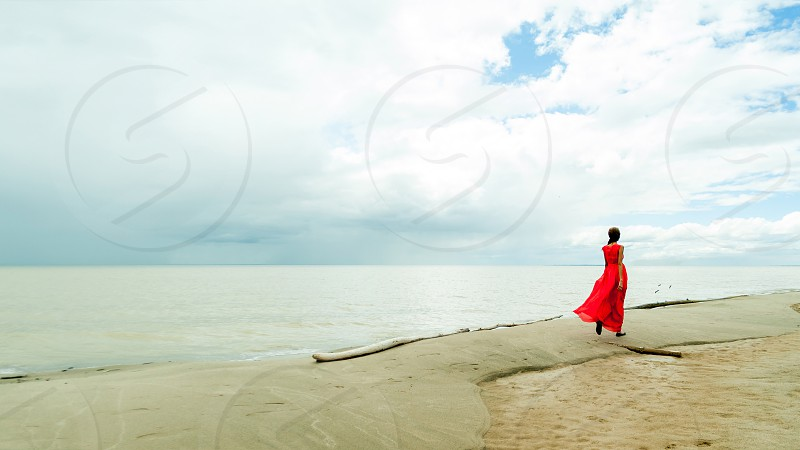 girl in a red dress walking along the beach against the sea photo