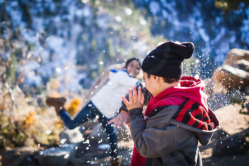 boy and girl throwing snow balls during daytime photo