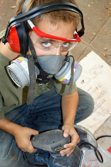 Little boy wearing noise protectors and a respirator uses a sander on his project. photo