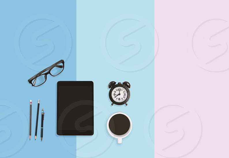 Modern home office working place concept. Table top work area with pastel color. Alarm clock Tablet Eyeglasses A cup of black coffee and pencils on sweet pastel background with copy space. photo