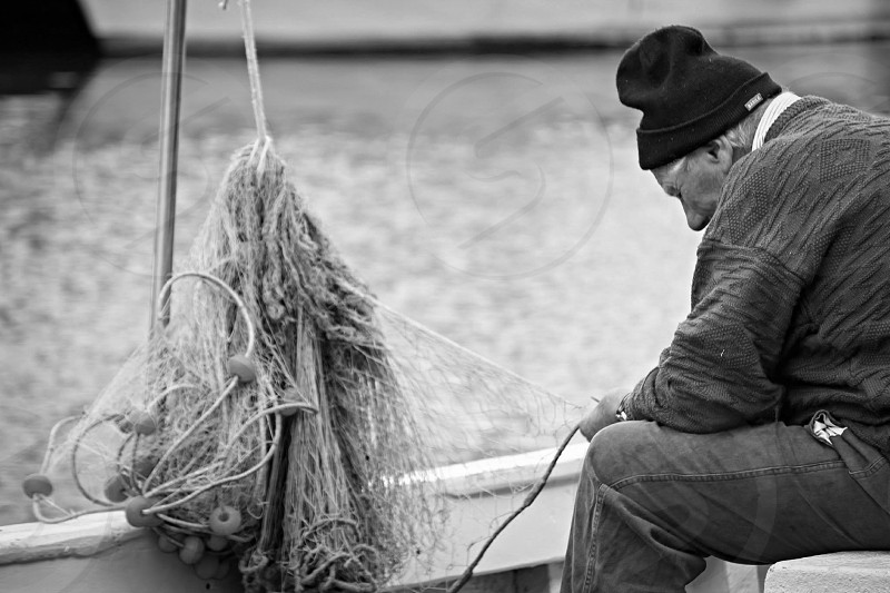 grayscale photo of fisherman fixing the net on his boat photo