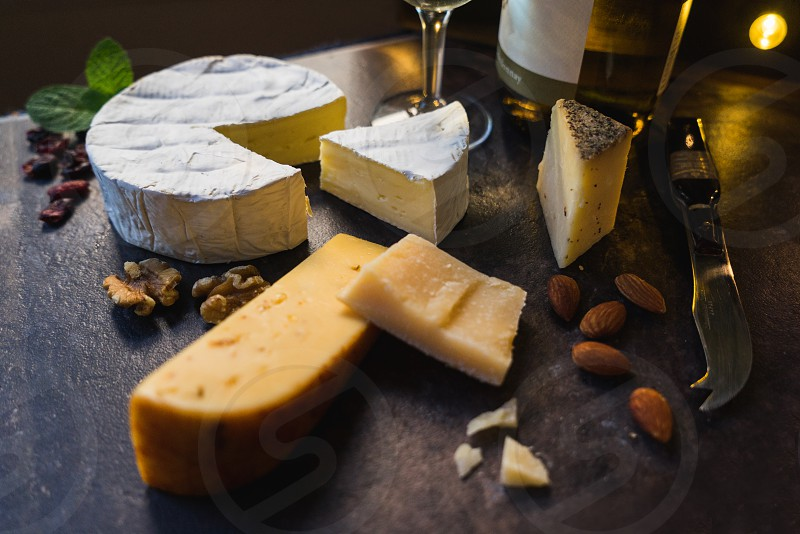 A still life of cheese and wine on a slate cheeseboard background photo