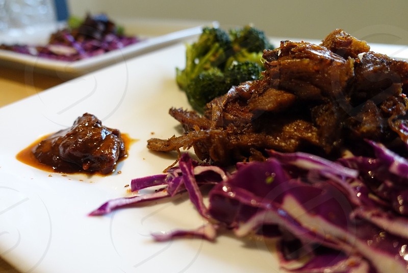 cooked meat with sauce and broccoli on white ceramic plate photo