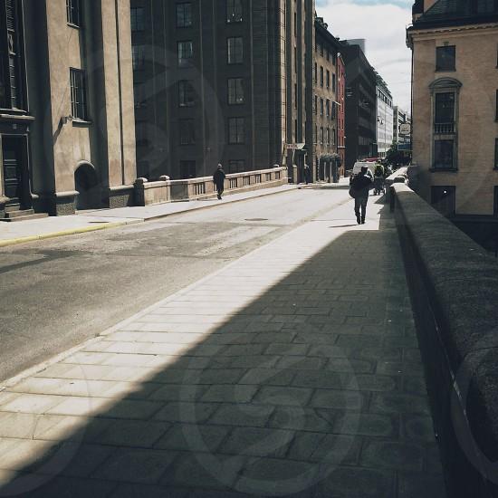 man in black shirt walking on sidewalk photo