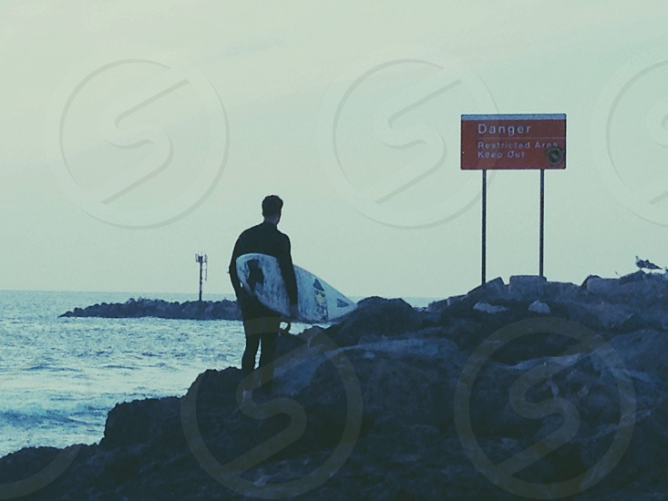 man in black wetsuit with surfboard on rocky beach with danger sign photo