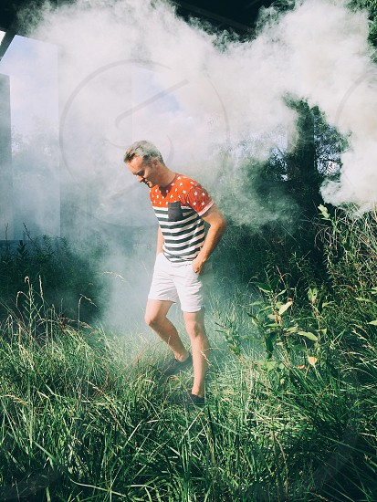man in striped dotted red white black t shirt and white shorts in grass near fog photo