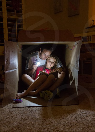 Father and daughter spending quality time reading on her washing machine box fort... photo
