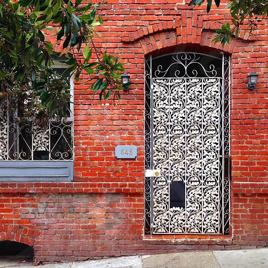 Brick building with ornate metal gate.  photo