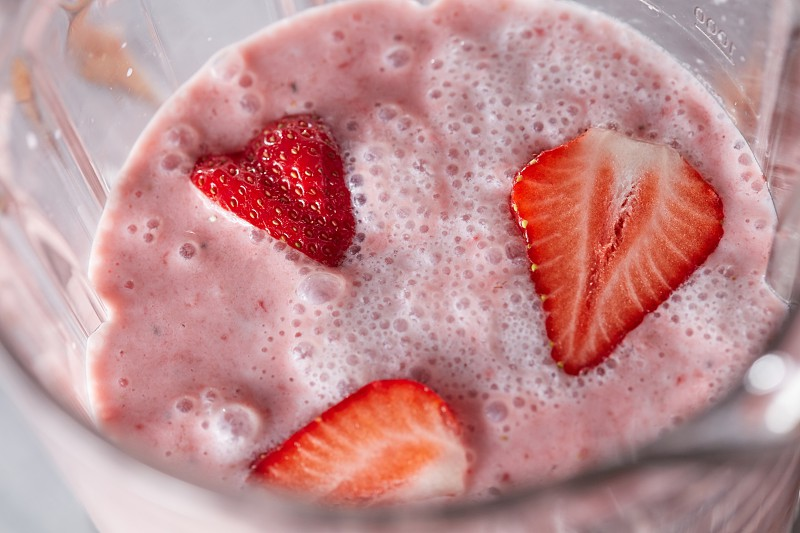 Closeup of milk drink with healthy strawberry slices in a blender. Home-made berry shake. Top view photo