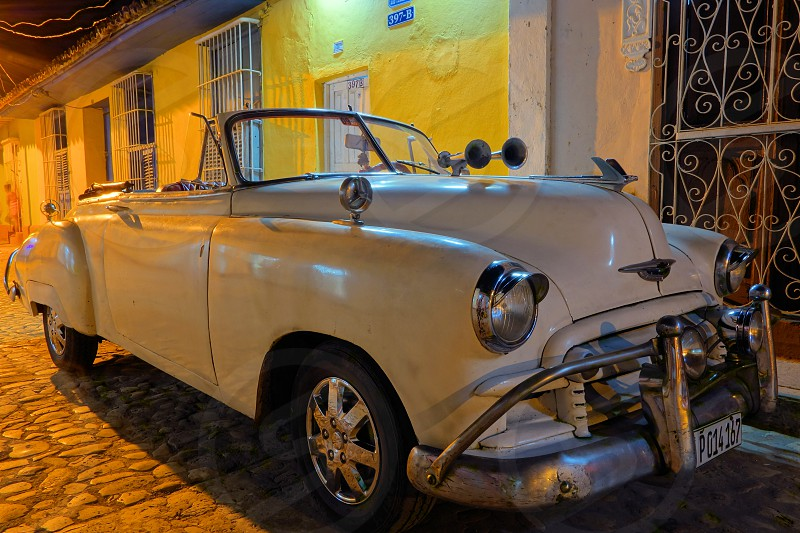 An American classic convertible car parked in the cobble street of historic parts of Trinidad Cuba on Christmas Eve 2013.  photo