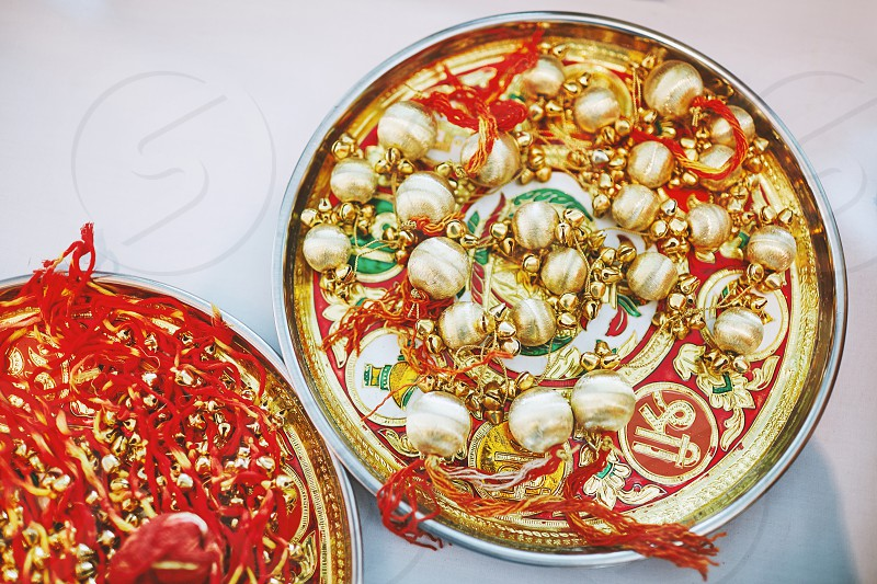 The golden choora with red thread on the plate the items for rituals of indian marriage ceremony photo