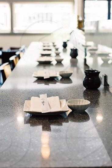 white square ceramic plates set on long grey table photo