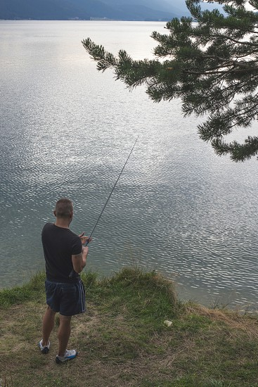 Man with fishhook in front of mountain dam. Bulgaria photo