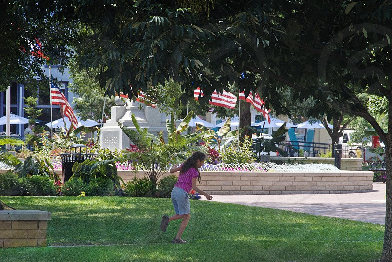 Little girl playing hopscotch on downtown square with American flags in background photo