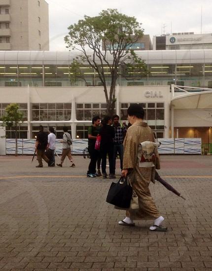 woman walking on brown concrete floor photo