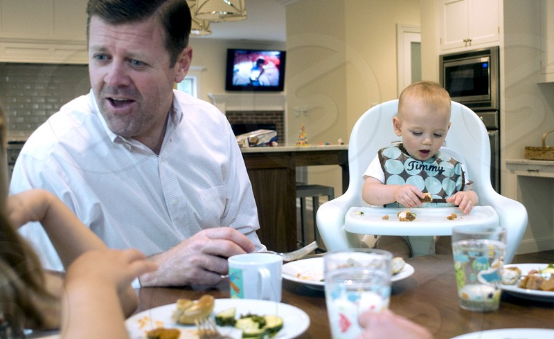 man in white dress shirt looking at girl eating on dining table near infant sitting on white highchair photo