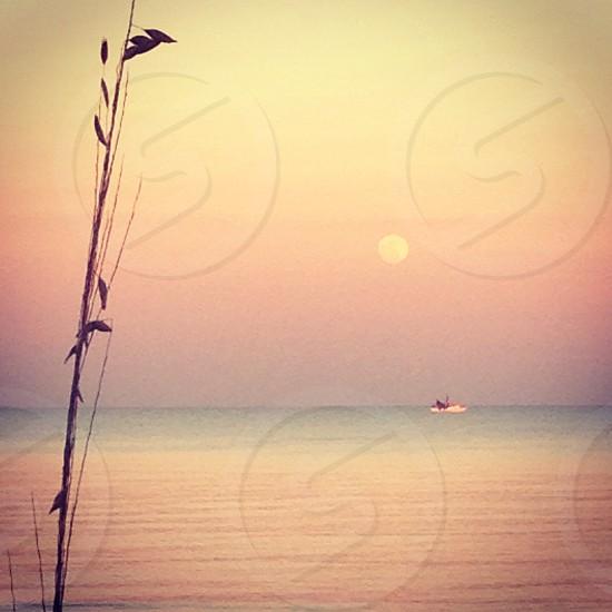 Florida moonrise at dusk - shrimp boat on calm seas photo
