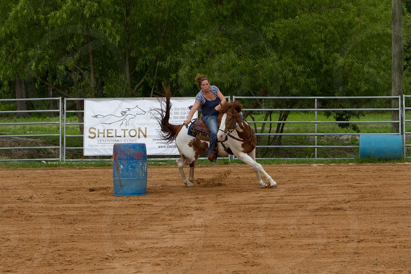 Veterinary clinic advertisement inside ring during horse barrel racing photo