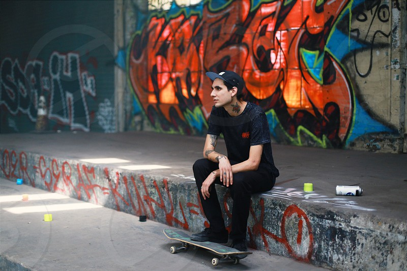 man wearing black crew neck t-shirt and black denim jeans sitting on pathway while stepping on black and green skateboard with a background of orange blue and black graffiti photo