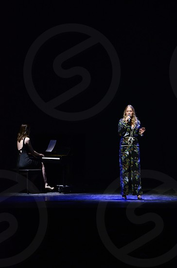 Two musicians pianist and singer performing music singing playing in the spotlight photo