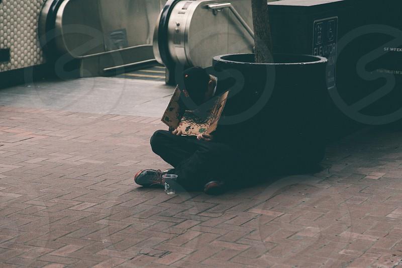 man wearing black baseball cap holding brown placard sitting on the floor beside escalator photo