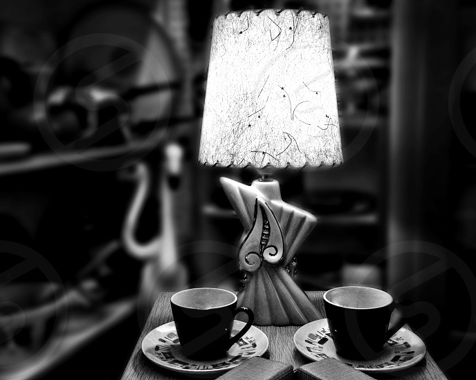 Black and white image of a retro lamp and two cups and saucers photo