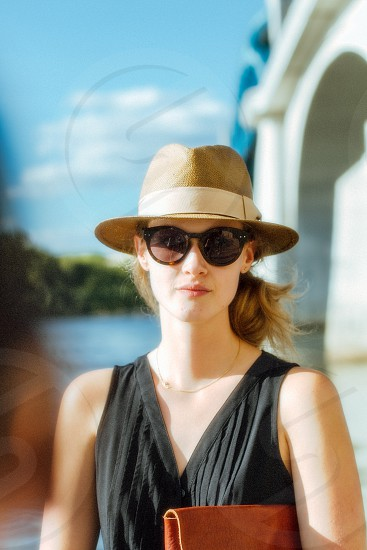 woman wearing a straw fedora sunglasses and a black sleeveless shirt photo