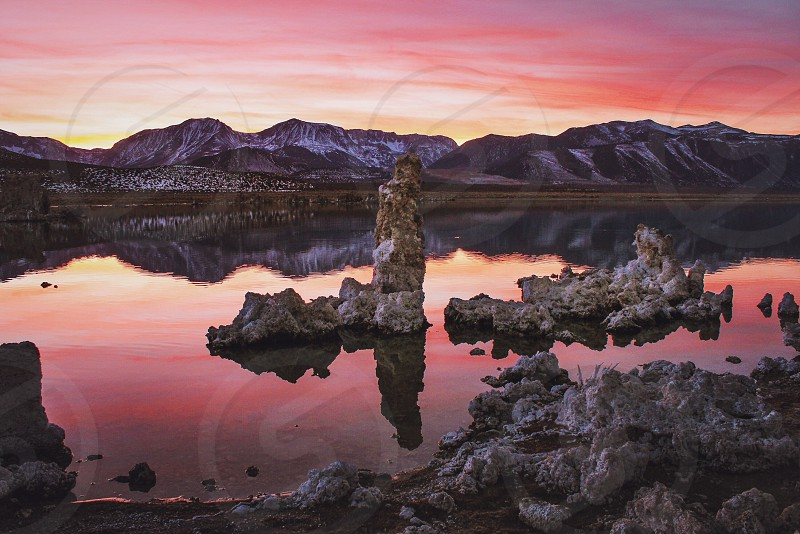 sunset pink red yellow lake mountains tufas clouds reflection still water photo