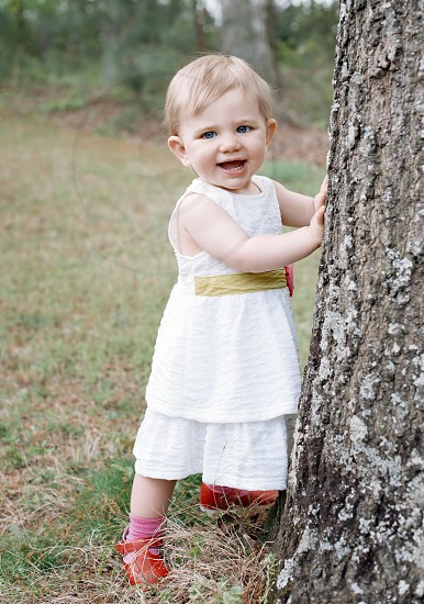 girl wearing a white dress holding a tree trunk photo