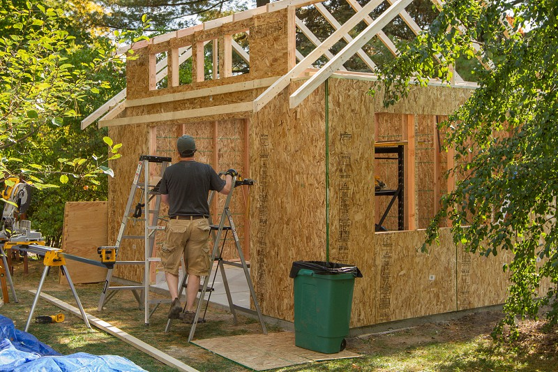 A man working on an outdoor shed photo