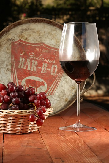 wine glass with brown liquid near grapes in brown wicker basket photo
