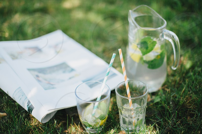 2 drinking glasses with straws near pitcher and newspaper on grass photo