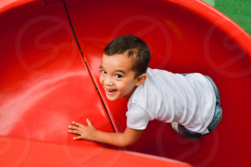 Little 3-year old boy playing at a playground active summer. photo