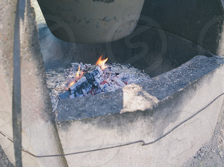 Concrete Cauldron Fireplace Outdoor with Small Fire Closeup photo