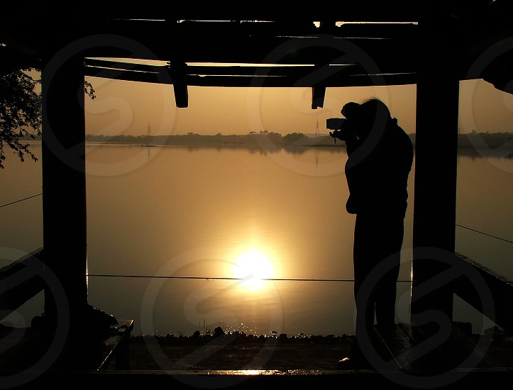 A photographer photographing the landscape during sunrise at the Rawal Lake in Islamabad Pakistan. photo