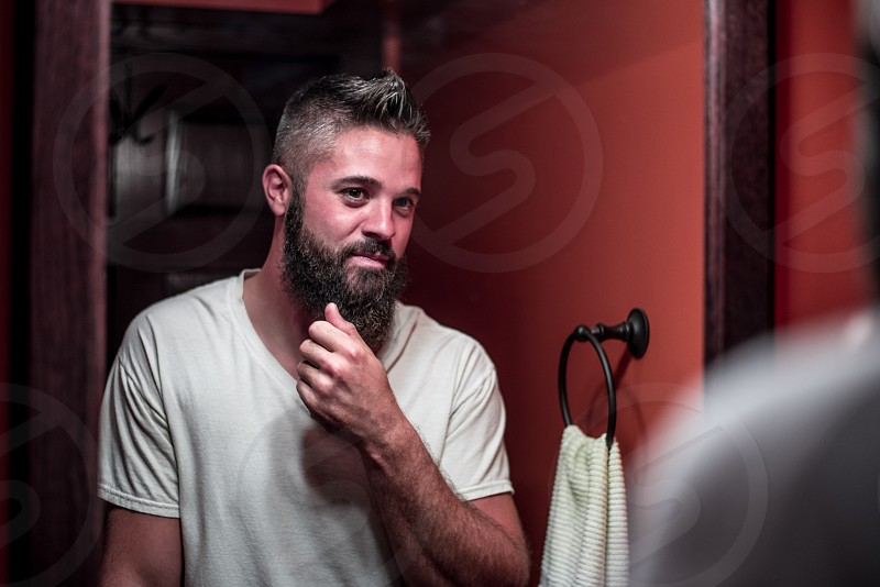 Young man with beard looking at himself in mirror in the bathroom. photo