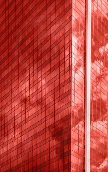 Urban glass business skyscraper with shadows and reflections of sky clouds on a shiny surface in a fashionable pantone trendy color of spring-summer 2019 season. photo